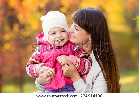 playful beautiful mother and kid girl outdoors in fall - stock photo