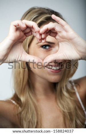 Playful beautiful young blond woman making a heart gesture with her fingers to show her love and affection or that she likes something