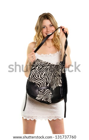 Playful blonde biting the strap of her black and white bag. Isolated