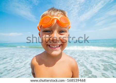 Playful boy in swimming goggles on the beach with sea on background - stock photo
