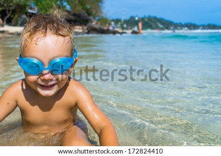 Playful boy in swimming goggles on the tropical beach - stock photo