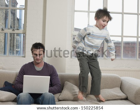 Playful boy jumping on sofa while father using laptop at home - stock photo