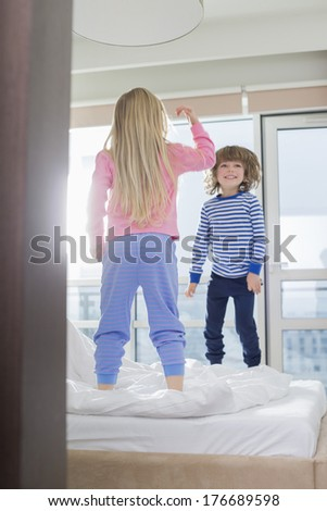 Playful brother and sister standing on bed - stock photo