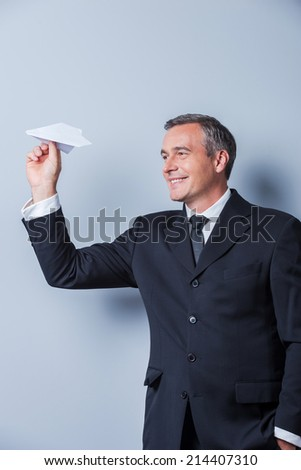 Playful businessman. Cheerful mature man in formalwear holding paper airplane and smiling while standing against grey background - stock photo