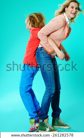 Playful Caucasian mother and son in studio on cyan background.