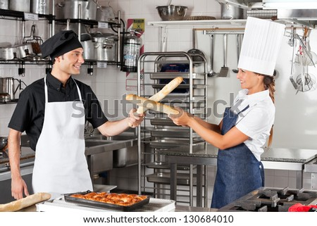 Playful chefs fighting with bread loafs in restaurant kitchen