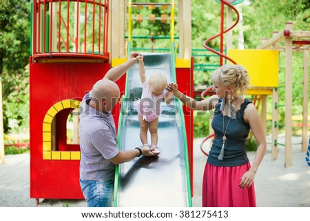 Playful child with parents at the playground outdoor. Mom, dad and child