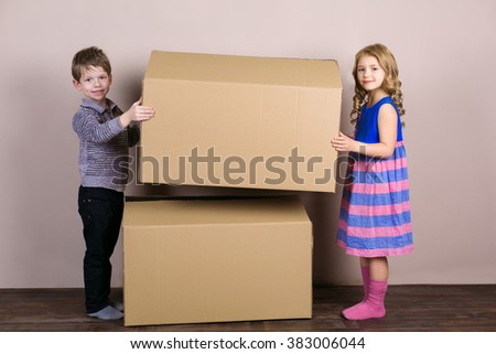 Playful childhood. Little children having fun with cardboard box. Children holding box and looking at camera - stock photo