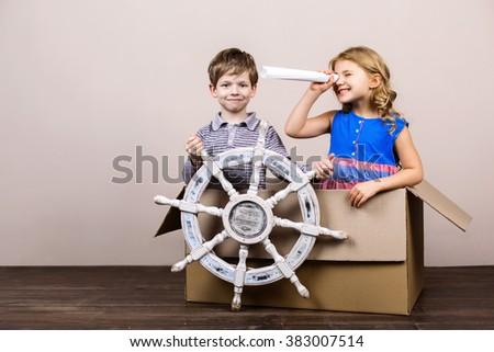 Playful childhood. Little children having fun with cardboard box. Children pretending to be on ship - stock photo