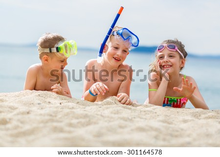 Playful children on the sand after scuba diving in the sea - stock photo