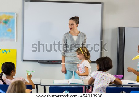 Playful children tied up female teacher with rope in classroom - stock photo