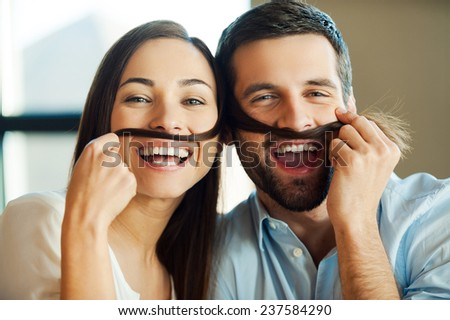 Playful couple. Beautiful young loving couple bonding to each other and smiling while making a fake mustaches from her hair - stock photo
