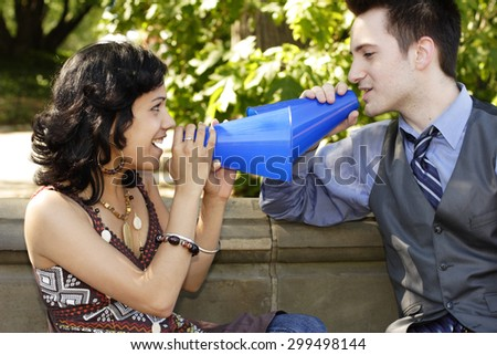 Playful couple communicating with megaphones. - stock photo