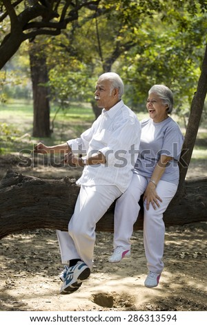 Playful couple having fun at park while sitting on tree trunk - stock photo