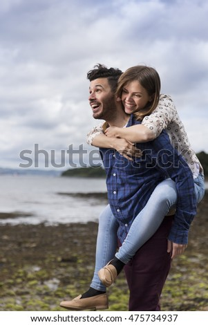 Playful couple hugging while walking along pebble beach.  Caucasian lifestyle concept.