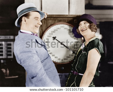 Playful couple standing on scale - stock photo