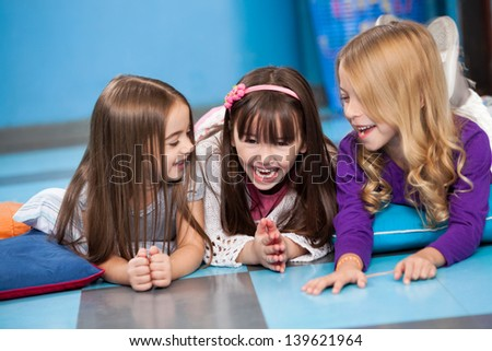Playful cute little girls laughing while lying on floor in preschool - stock photo