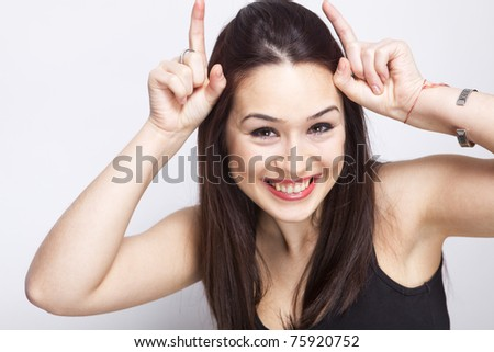 Playful cute woman having fun with imaginary horns