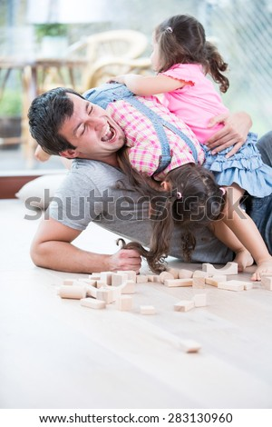 Playful daughters on top of father at home - stock photo