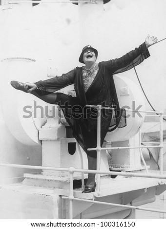 Playful energetic woman on boat - stock photo