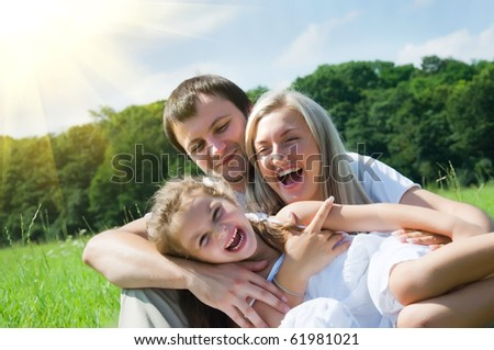 playful family on the meadow - stock photo