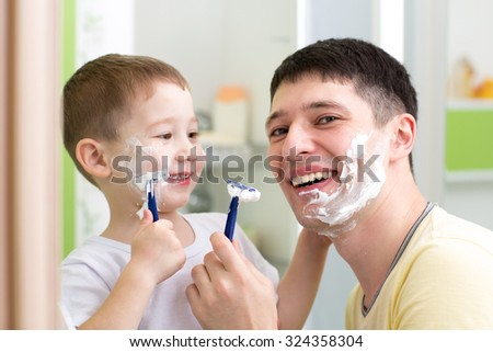 playful father and child son shaving together at home bathroom - stock photo