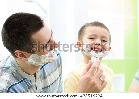 playful father and his son having fun in bathroom