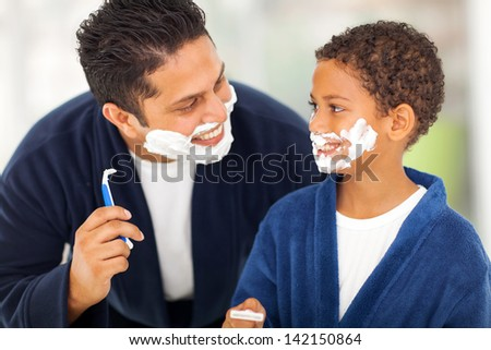 playful father and son shaving together at home bathroom - stock photo