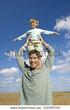 Playful father balancing son on shoulders in field - stock photo