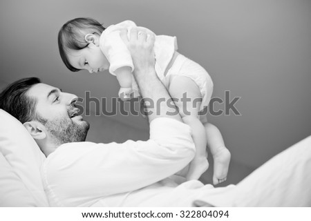 Playful father with his beloved daughter on white bed in white bedroom, lightly noised black and white portrait - stock photo