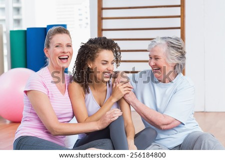 Playful female friends sitting together in gym - stock photo