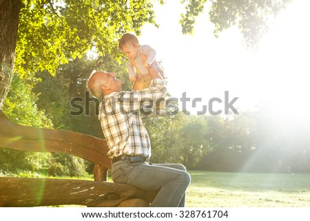 Playful grandfather spending time with his grandson in park on sunny day - stock photo