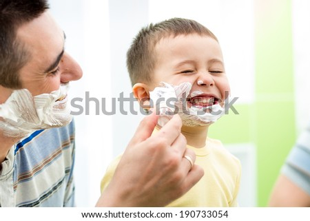 playful kid and father shaving together at home bathroom - stock photo