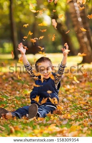 Playful kid playing with autumn leaves in a park - stock photo