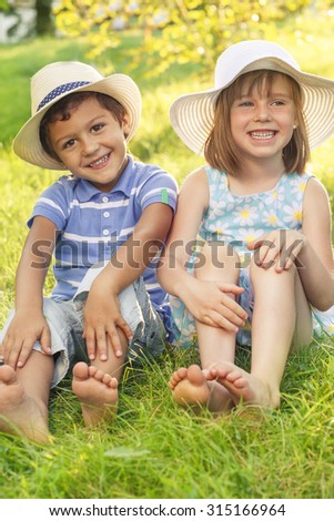 Playful kids sit on summer grass - stock photo