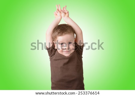 playful little boy smiling with his hands up on a green background - stock photo