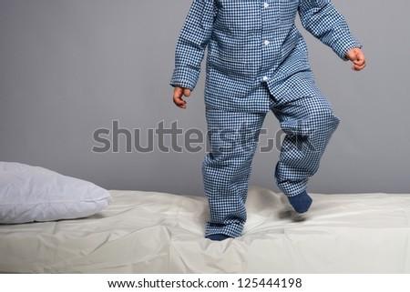 Playful little boy wearing blue pyjamas in bed - stock photo