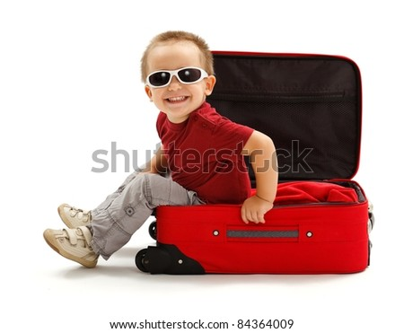 Playful little boy wearing sunglasses, sitting in red suitcase - stock photo