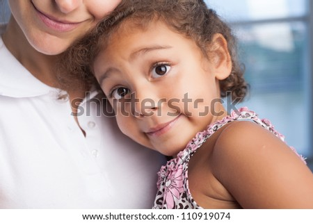 Playful little girl embracing her mother - stock photo