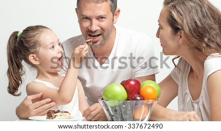 Playful little girl feeding her father with cake - stock photo