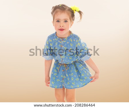 Playful little girl in a blue dress with bunches.kindergarten, the concept of childhood and joy, teens