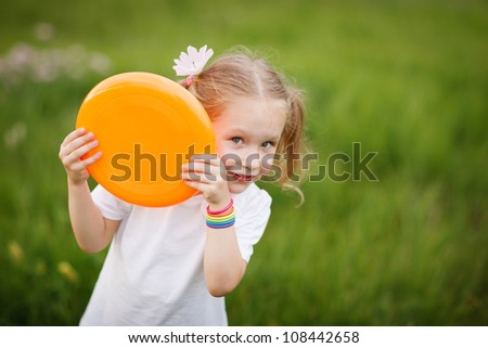 Playful little girl peeping out from flying plate outdoors, against green grass background - stock photo