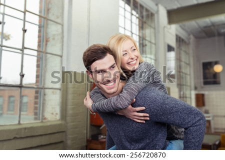 Playful loving couple enjoying a piggy back ride inside their spacious apartment with the husband giving his smiling wife a lift on his back - stock photo