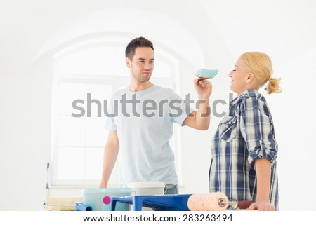 Playful man putting paint on woman's nose in new house - stock photo