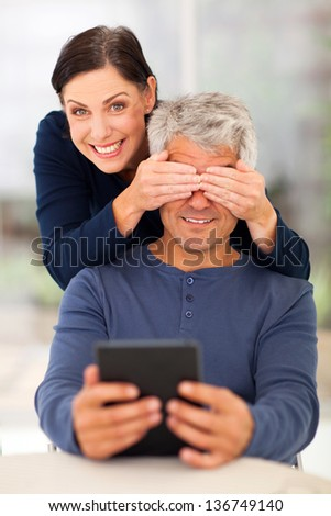 playful middle aged couple having fun at home