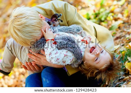 playful mother and baby having fun in autumn park