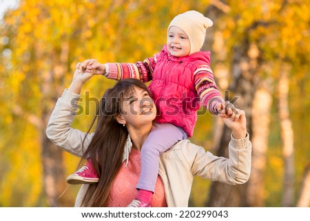 playful mother with child girl walking outdoors in autumnal park