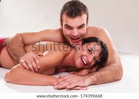 Playful romantic man and woman lying naked on their stomachs in each others arms laughing at the camera / Playful romantic man and woman