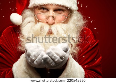 Playful Santa Claus blowing snow and looking at camera - stock photo