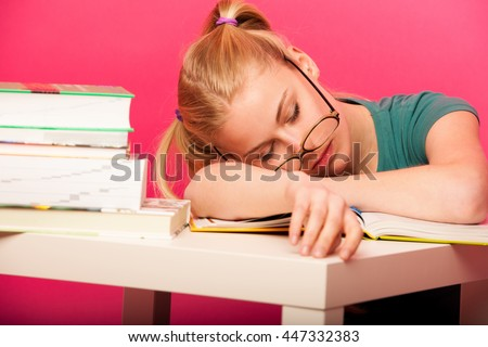 Playful schoolgirl with two hair tails and big eyeglasses sitting behind the small table full of books fall asleep while studying.  Tired of reading boring book.